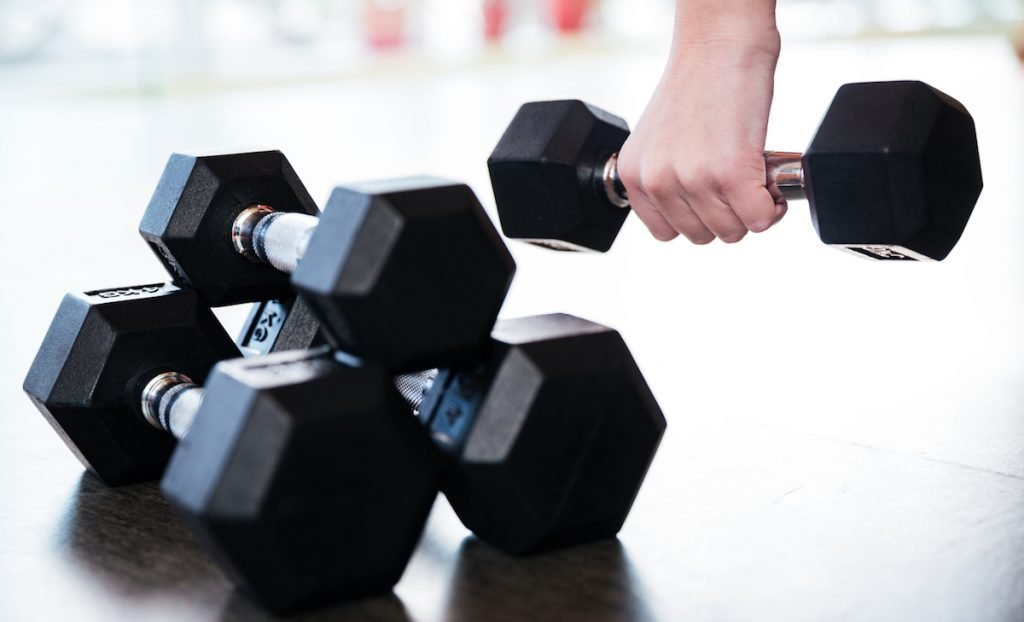 Two pairs of metal dumbbells on the floor used by young sportswoman